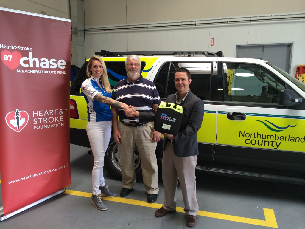 Gisele Philp, Primary Care Paramedic, Northumberland Paramedics Presents AED to member Tim Duffin, member, and Commodore Tom  Willison,